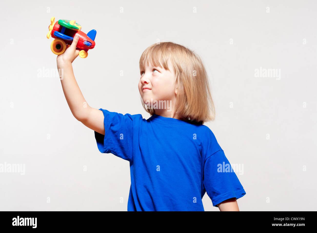 Junge mit langen blonden Haaren spielen mit Spielzeugflugzeug - isoliert auf hellgrau Stockbild