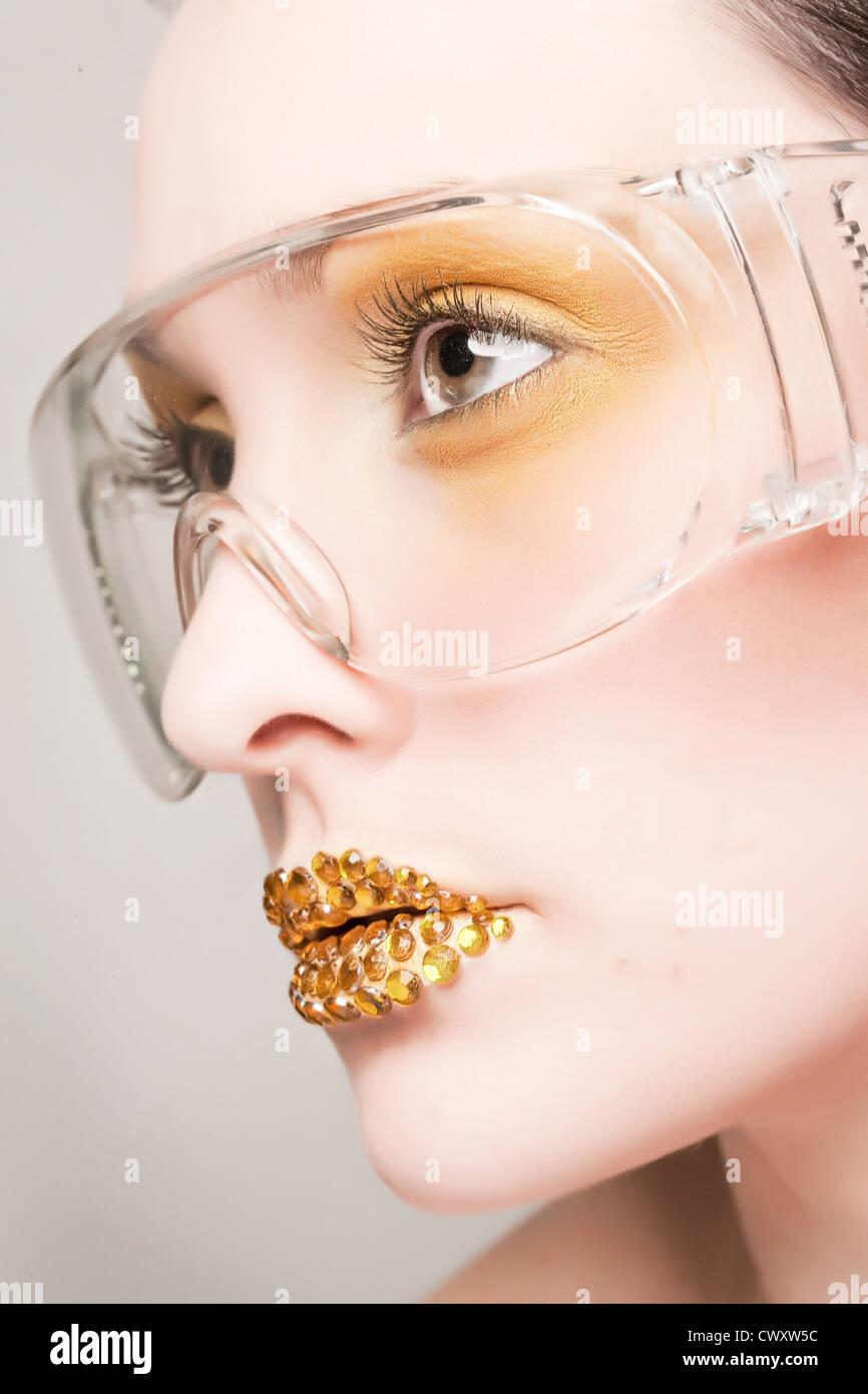 Kaukasische Mädchen mit gold Fashion Make-up tragen klare Gläser und gold Diamonties auf den Lippen Stockbild