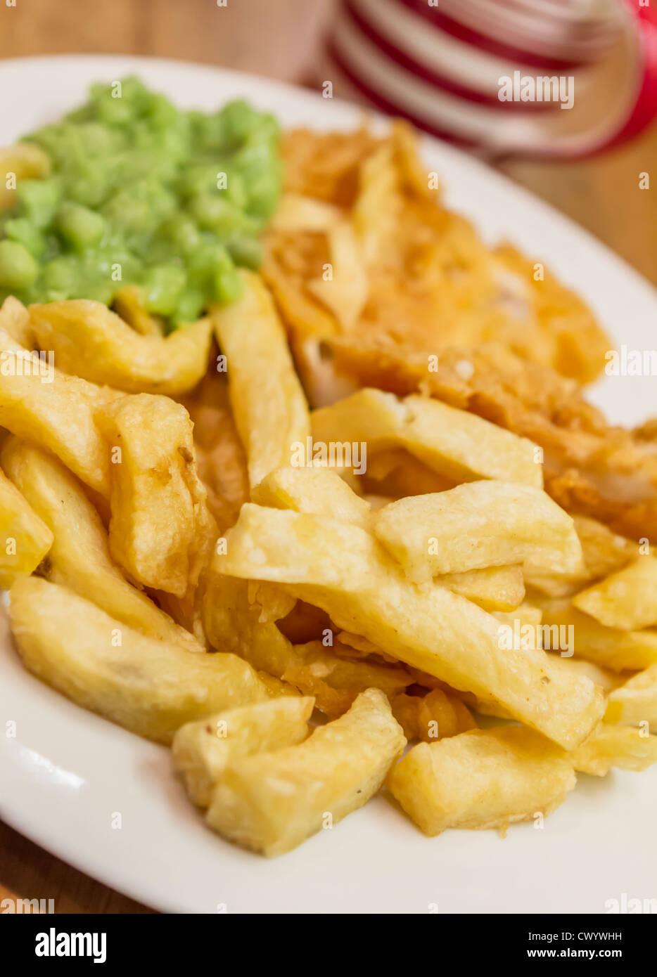 Ein Teller mit traditionell frittierten Fish And Chips mit Erbsenpüree und eine Tasse Tee Stockbild