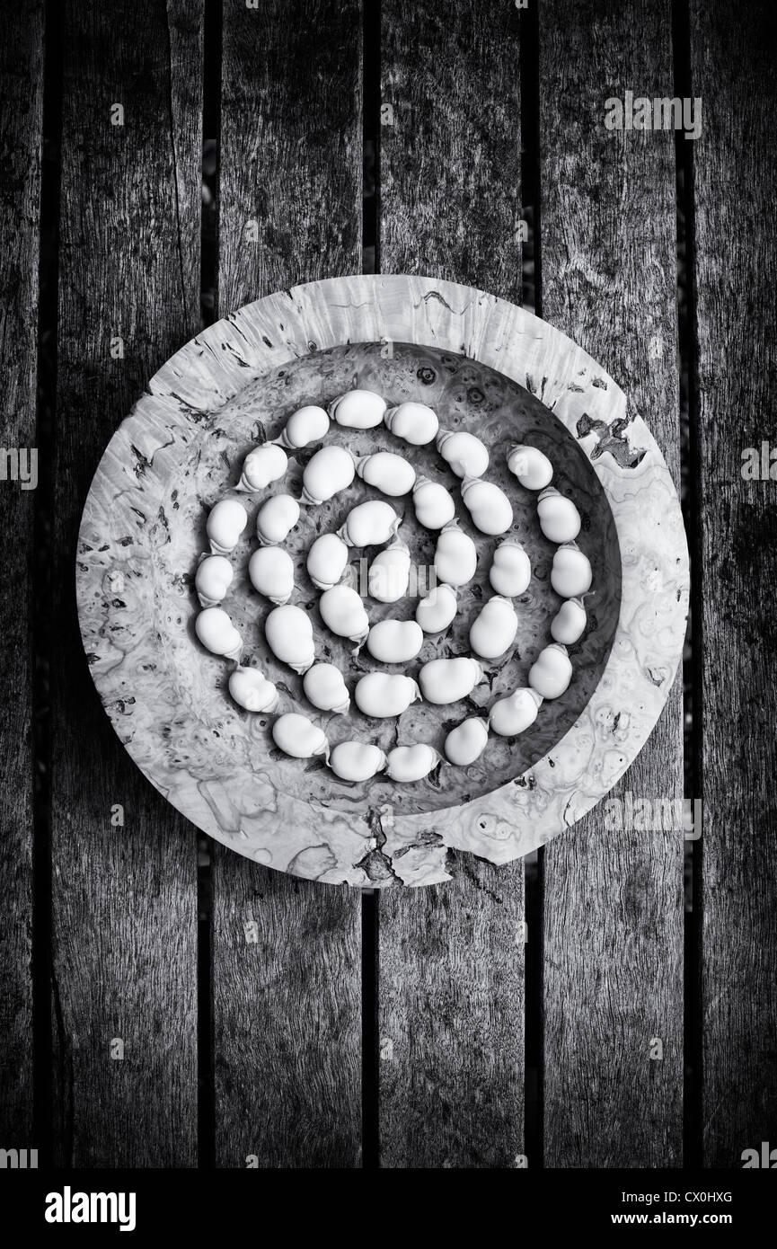 Saubohne Spirale in einer Holzschale auf einem Gartentisch. Monochrom Stockbild