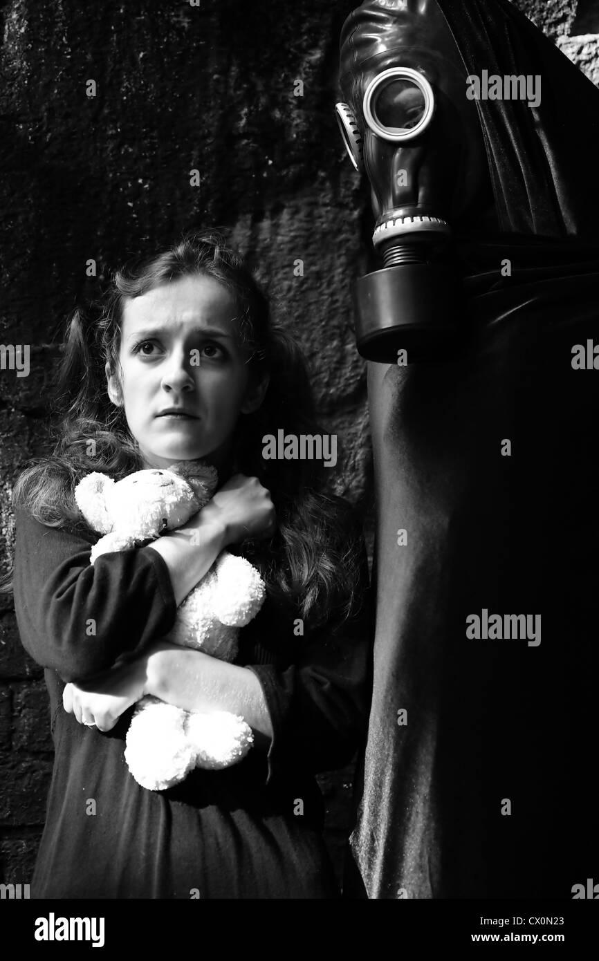 Porträt der jungen Frau (Mädchen) mit Spielzeug und Stalker mit Gasmaske im Gesicht Stockbild