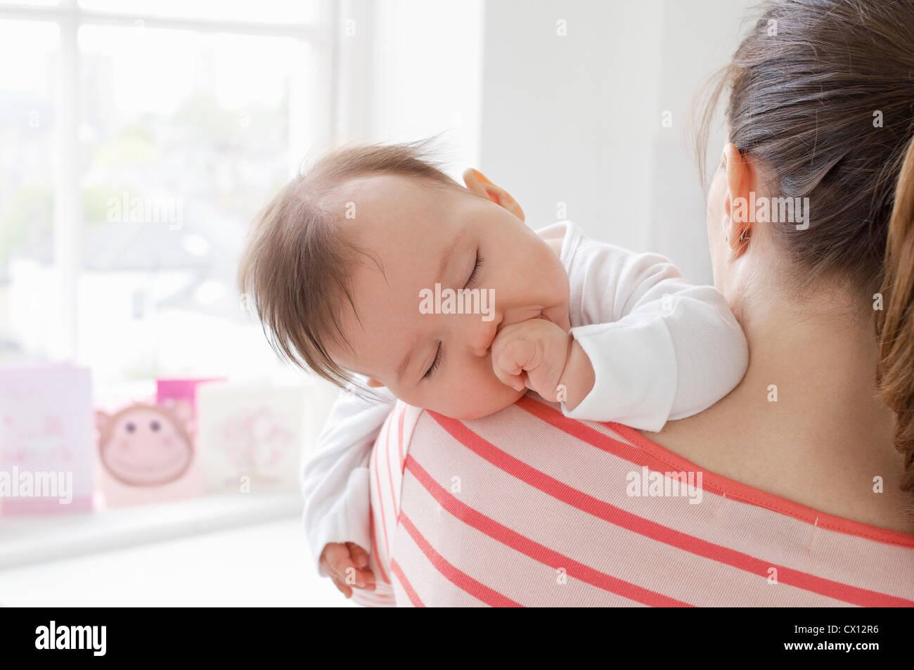 Babymädchen schläft auf Mutters Schulter Stockbild