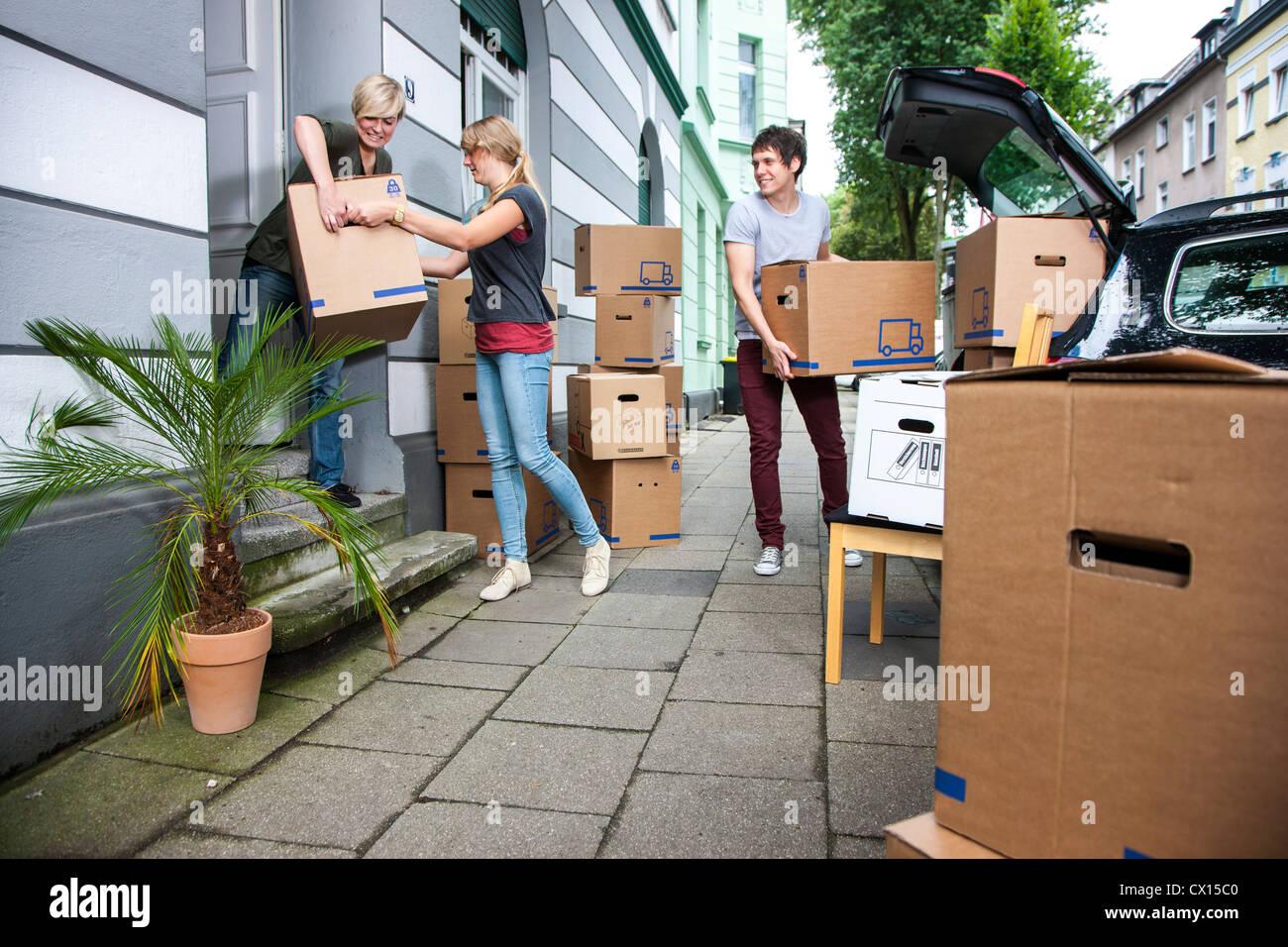 Umzug in eine neue Wohnung. Freunde helfen mit Umzugskartons, Möbel ...