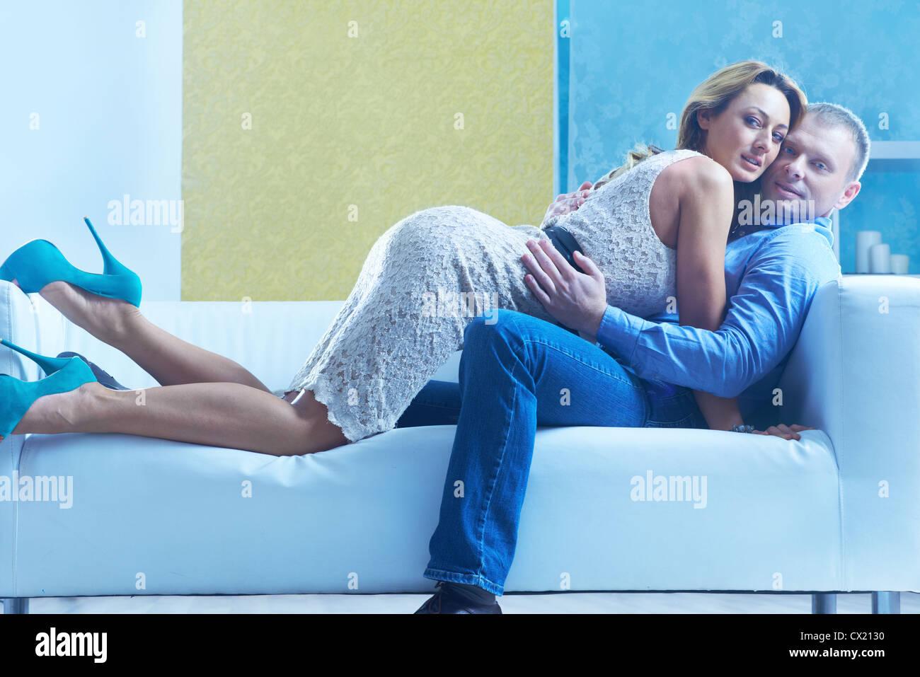 Leidenschaftliche Paare umarmen auf Sofa und Blick in die Kamera Stockbild