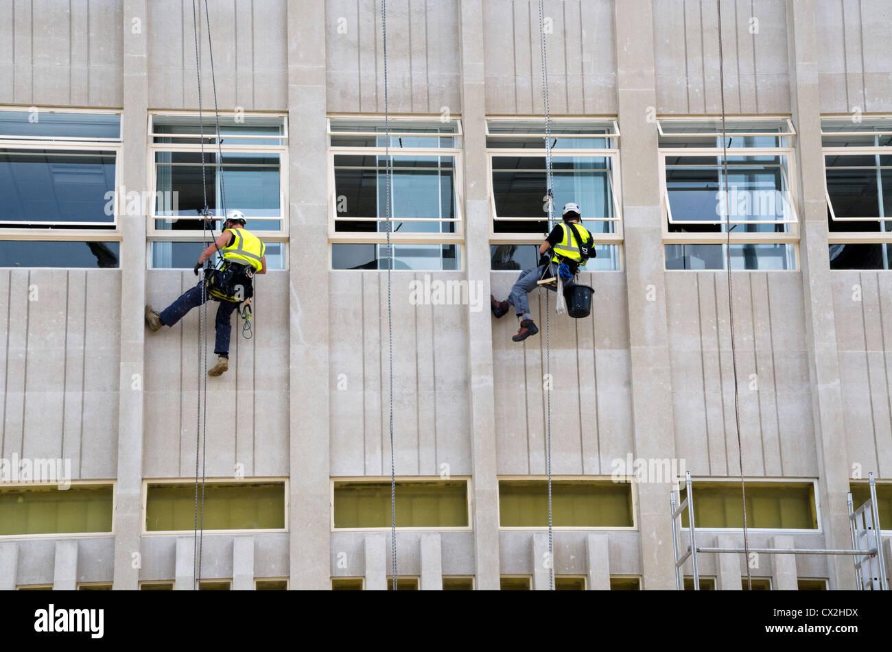 ZWEI Arbeiter HANGING ON THE Reparatur der Gebäude Wand Stockbild