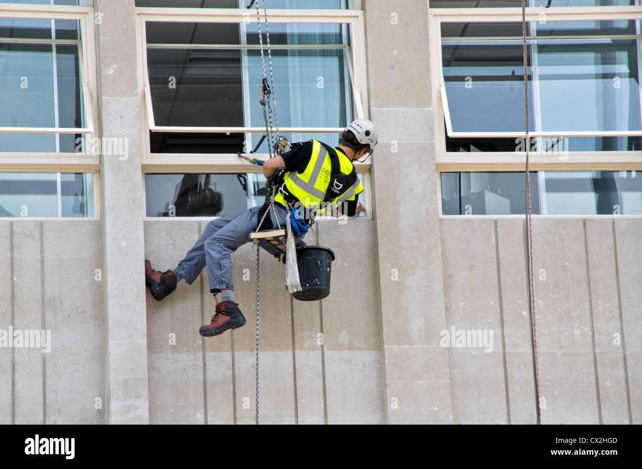 Ein Arbeiter HANGING ON THE Reparatur der Gebäude Wand Stockbild