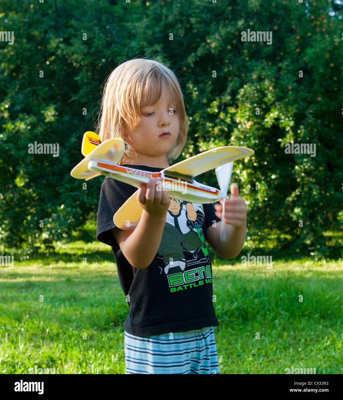 Junge mit langen blonden Haaren spielen mit Spielzeugflugzeug Stockbild