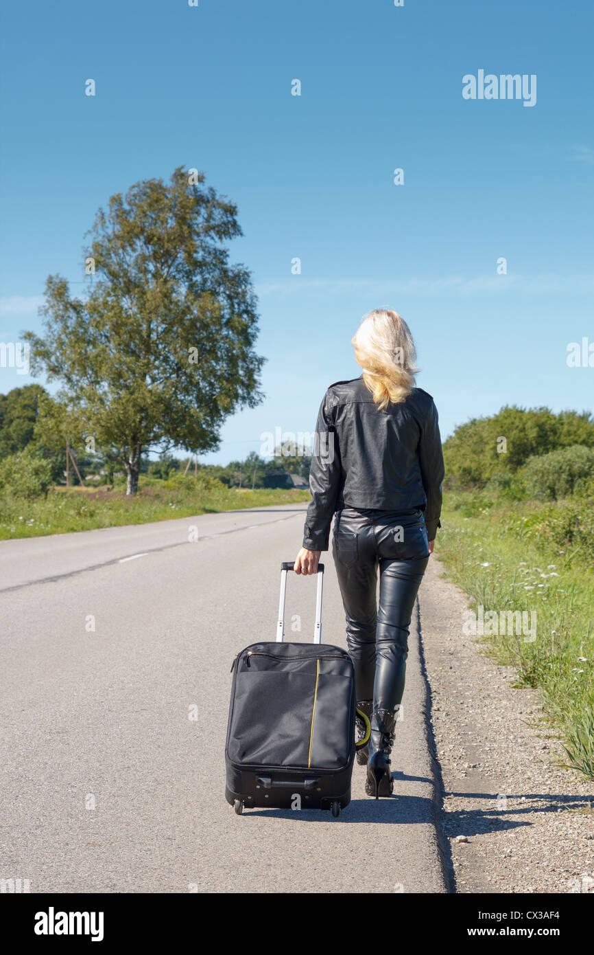 Frau, gekleidet in Lederkleidung zu Fuß entlang der ländlichen Straße Stockfoto