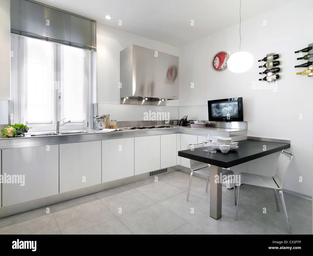 weiße moderne Küche aus Laminat mit Esstisch und Stühlen ...