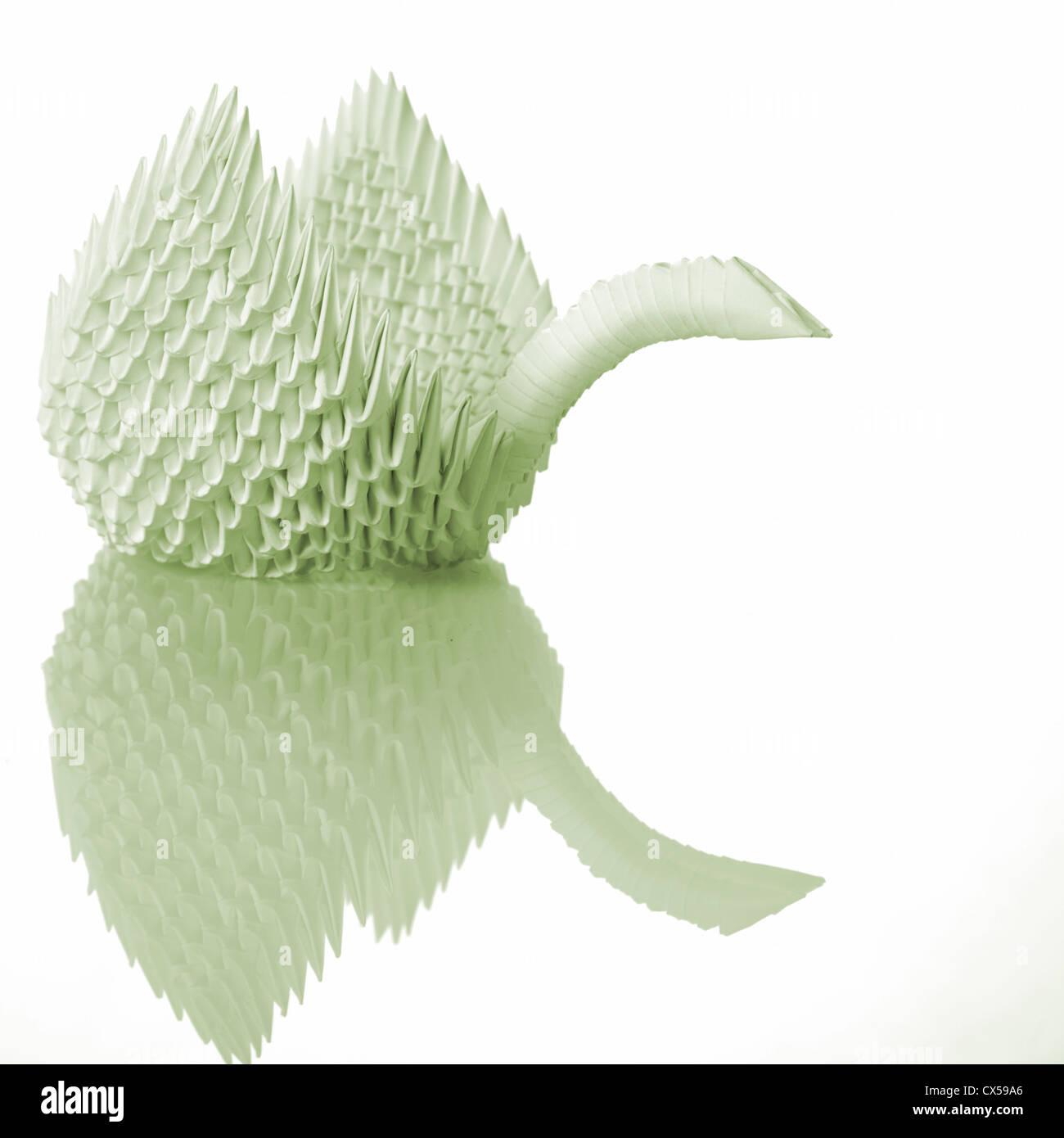 Origami-Kunst-Schwan auf Tisch mit Reflexion Stockbild