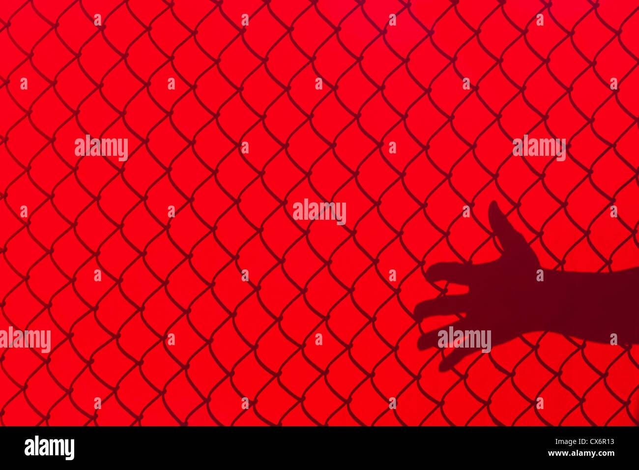 Rot-Zaun und Hand Schatten, Begriff der Freiheit Stockbild