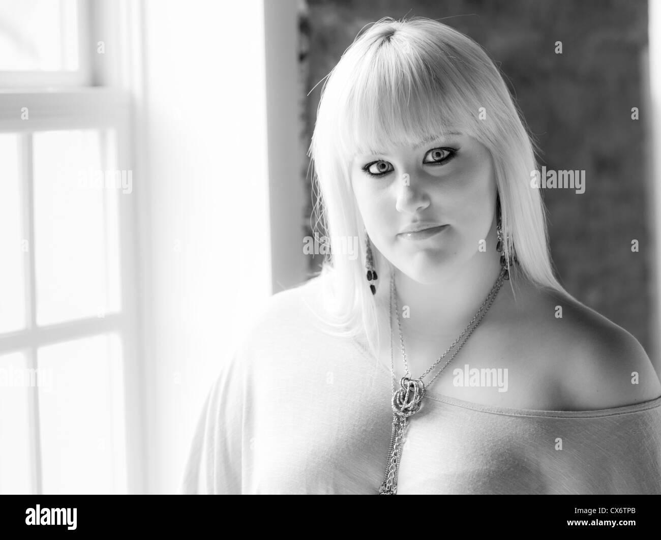 Attraktive junge Frau am Fenster stehen Stockbild