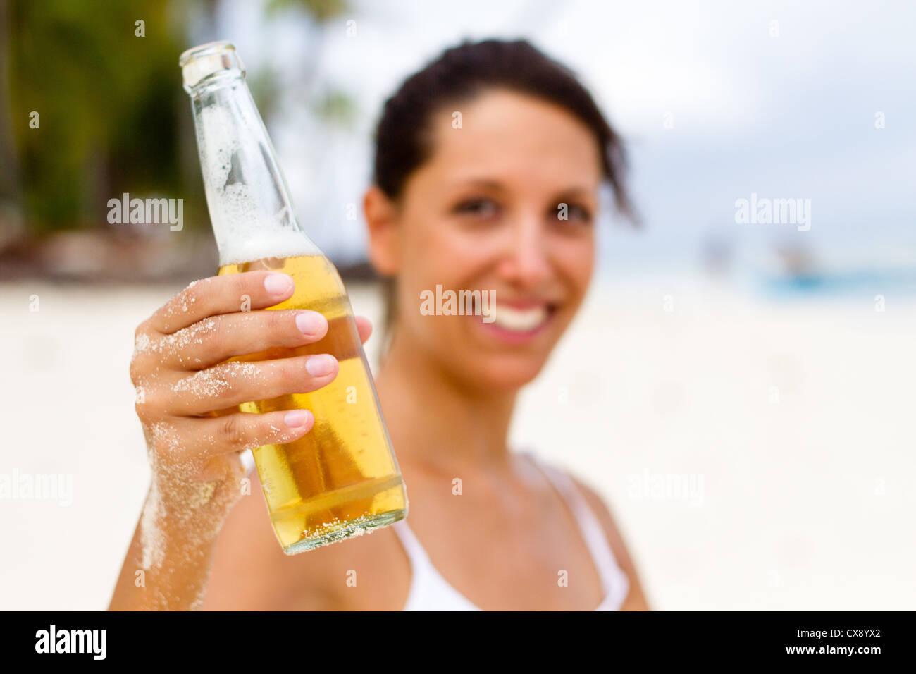 junge Frau mit Bier am Strand Stockbild