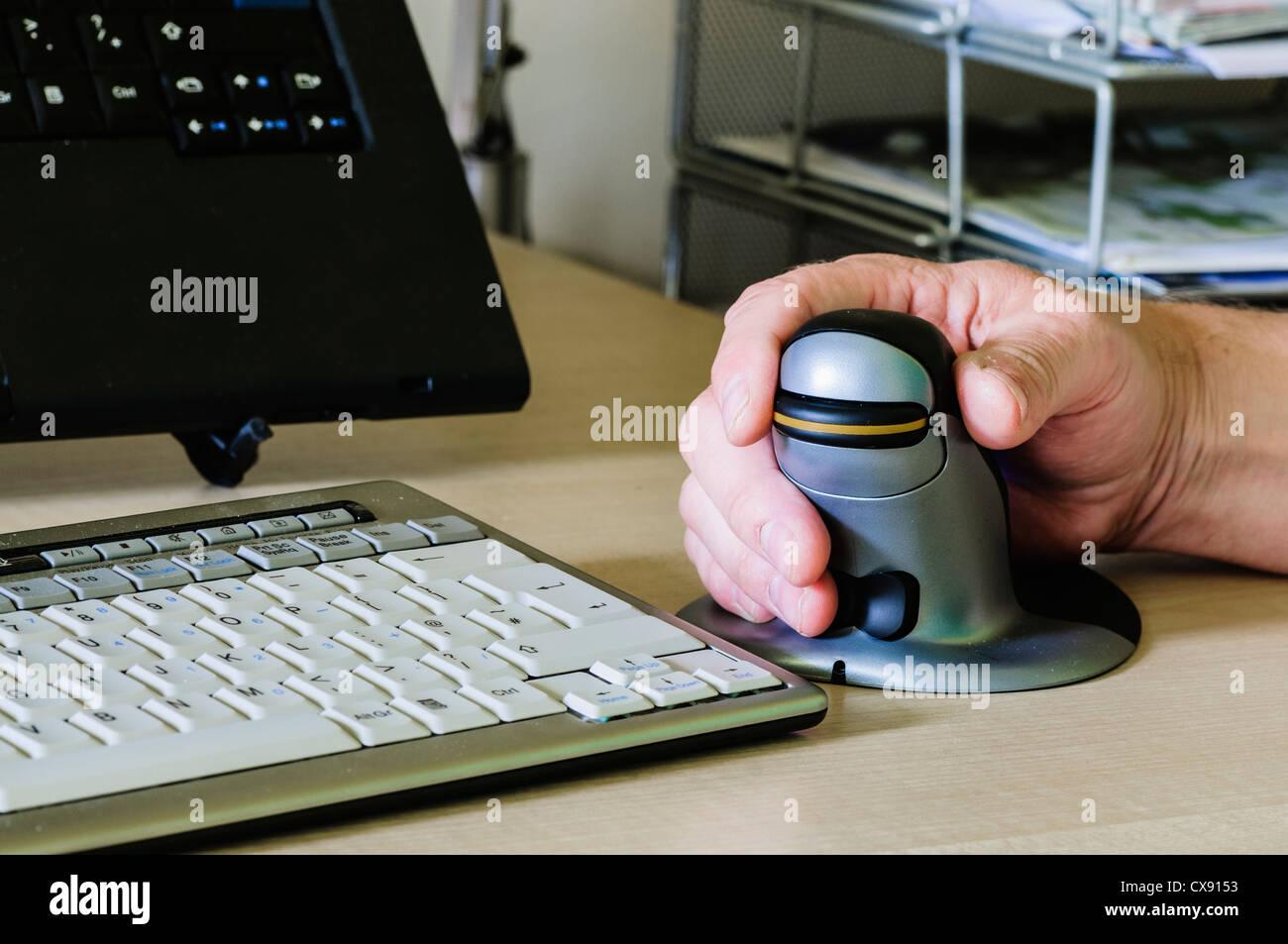 Man verwendet eine Pinguin vertikale ergonomische Computermaus für Menschen mit Schmerzen am Handgelenk Stockbild