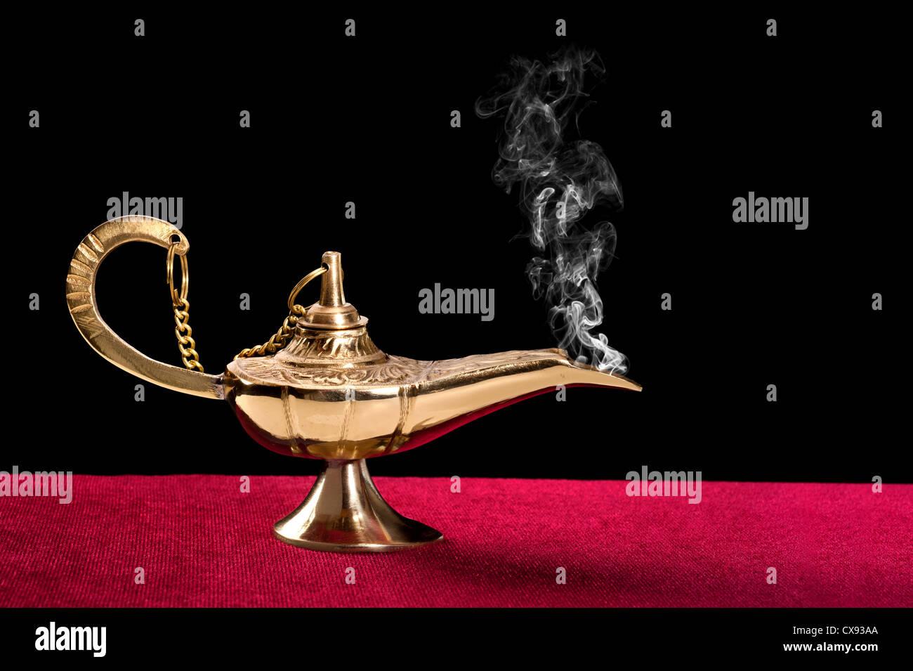 Eine uralte magische Lampe auf einem roten Filz Tischplatte verteilt einen Strom von geheimnisvollen Rauch. Stockbild