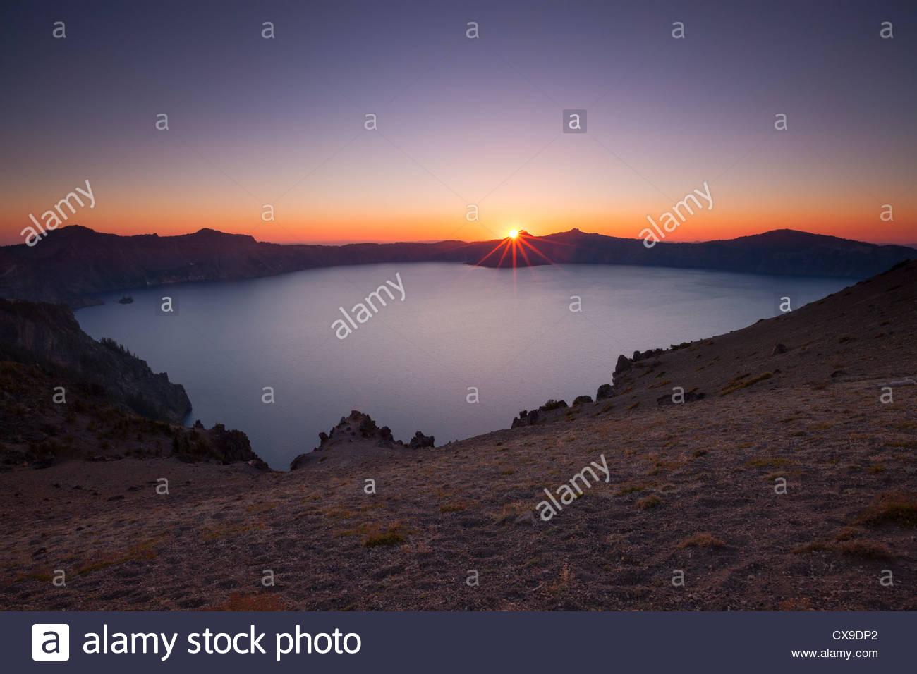 Die Sonne geht hinter den Rand des Crater Lake in dieser Ansicht aus der Cloud Cap übersehen in Crater Lake Stockbild