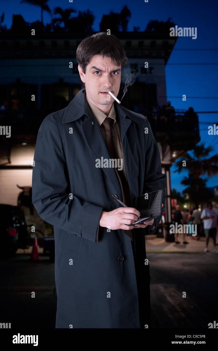 Schauspieler John Scamardella porträtiert einen ernsten Mann im Trenchcoat, auf den Straßen von Key West. Stockbild