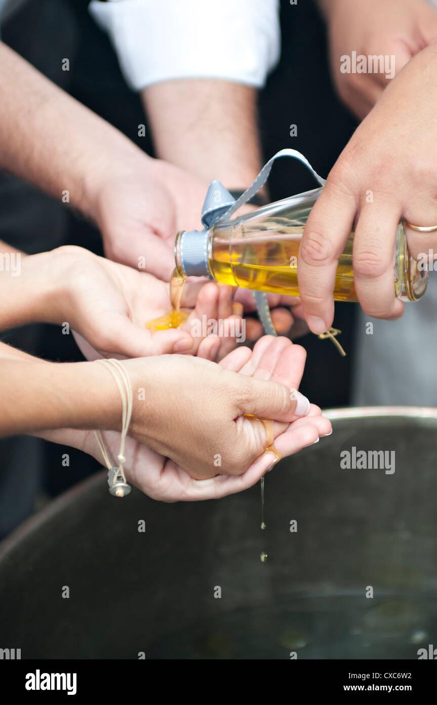 Orthodoxe Taufe Ritual. Der Priester gießt Olivenöl in den Händen der Paten über das Taufbecken Stockbild