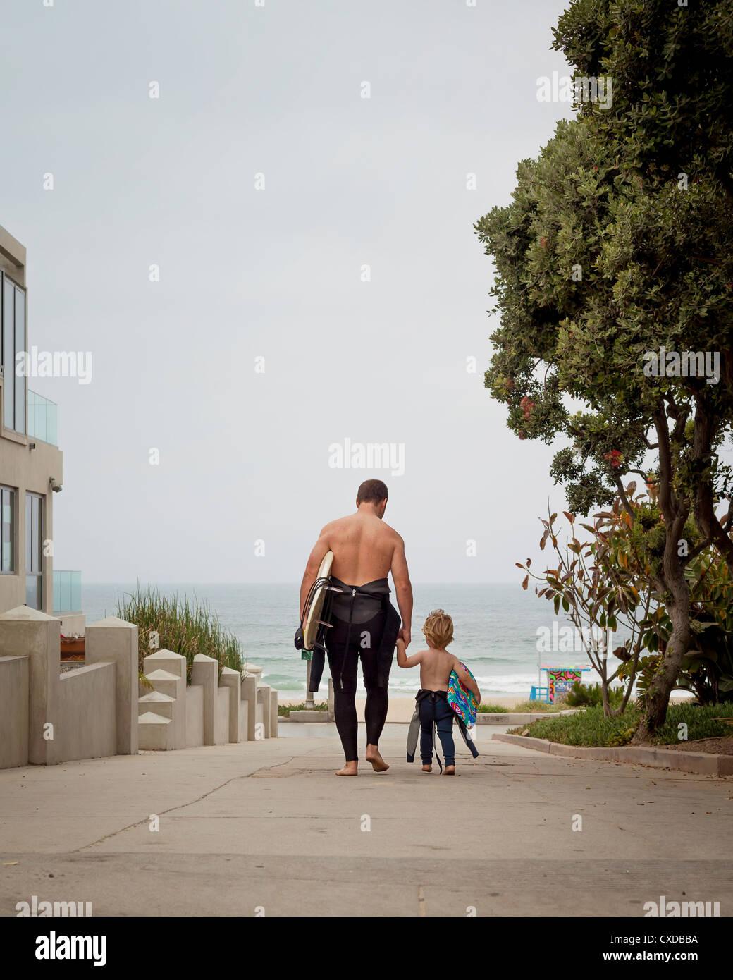 Kaukasische Vater und Sohn in Neoprenanzüge zu Fuß in Richtung Meer Stockfoto