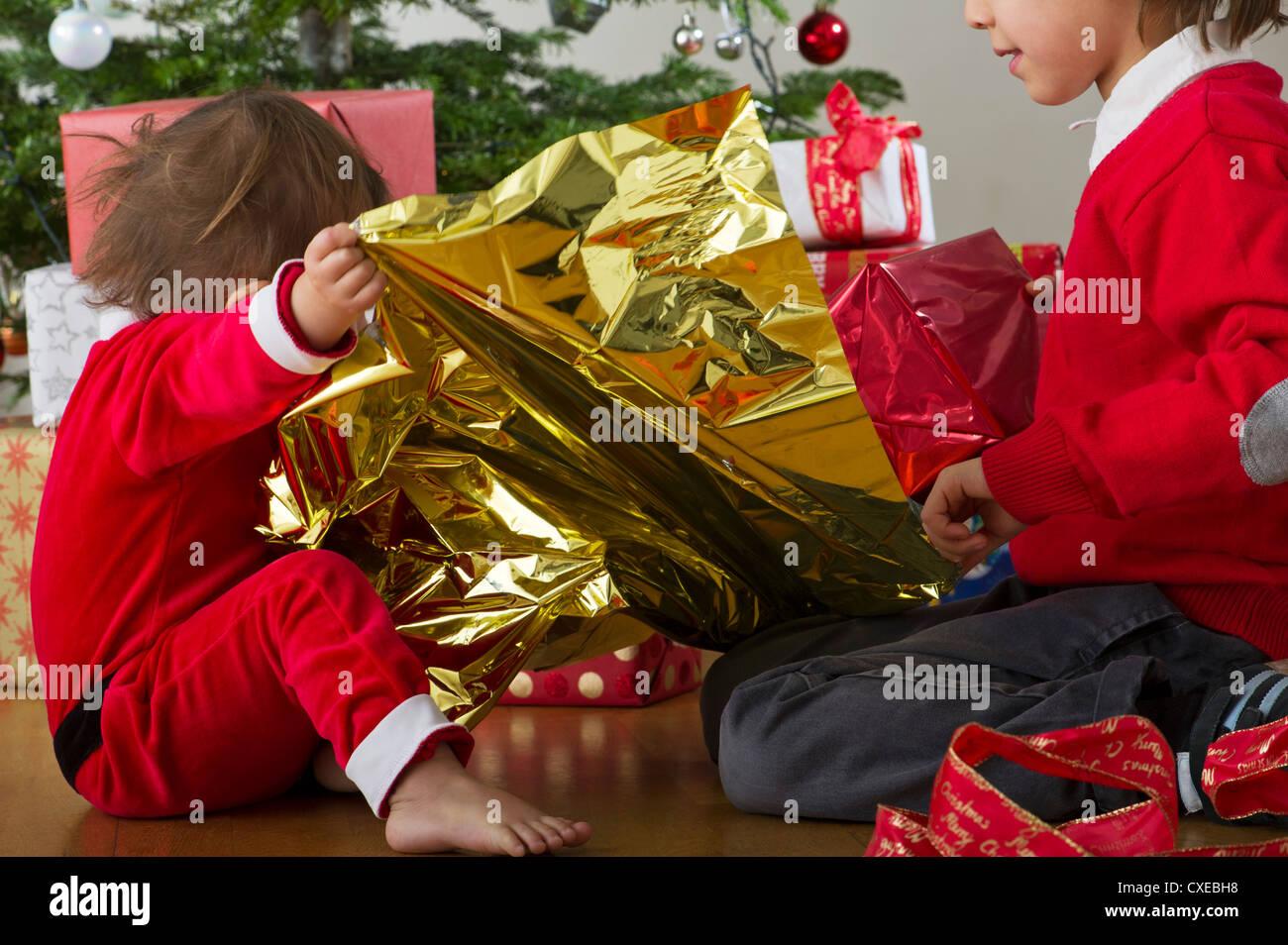 Junger Bruder und Schwester zusammen Weihnachtsgeschenke zu öffnen ...