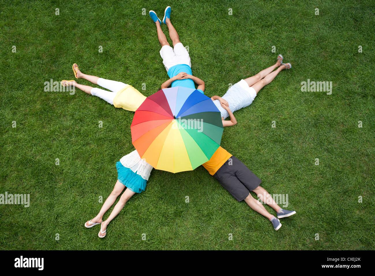 junge Menschen liegen unter Sonnenschirm Stockbild