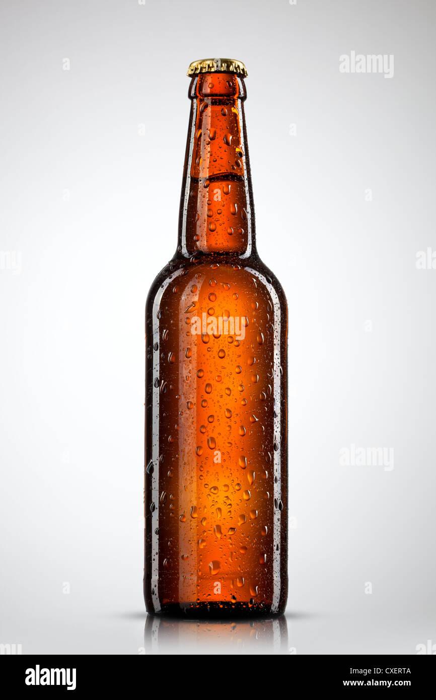 Bierflasche mit Wassertropfen isoliert auf weiss Stockbild