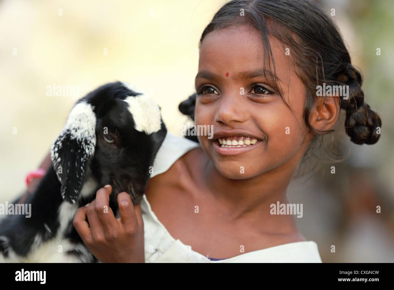 Indische Schulmädchen spielen mit ihrem Haustier Ziege Andhra Pradesh in Indien Stockbild