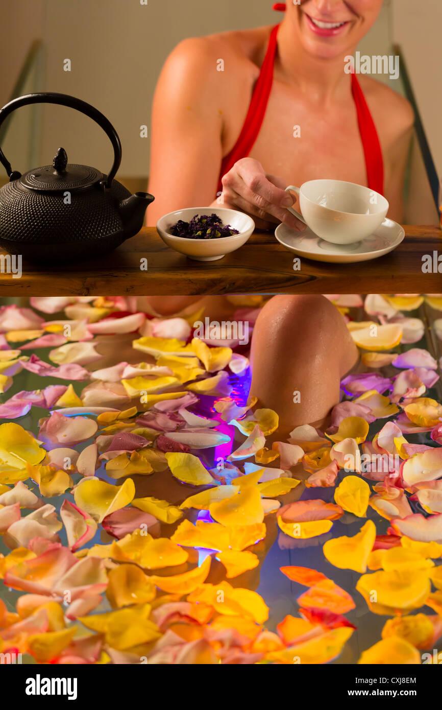 Frau Baden im Spa mit Farbtherapie, die Badewanne ist mit bunten Lichtern, viele Blüten auf Wanne und Tee beleuchtet. Stockfoto