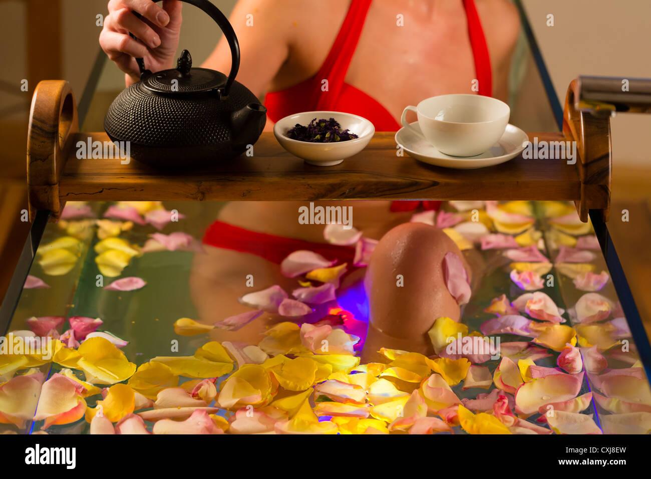 Frau Baden im Spa mit Farbtherapie, die Badewanne ist mit bunten Lichtern, viele Blüten auf Wanne und Tee beleuchtet. Stockbild