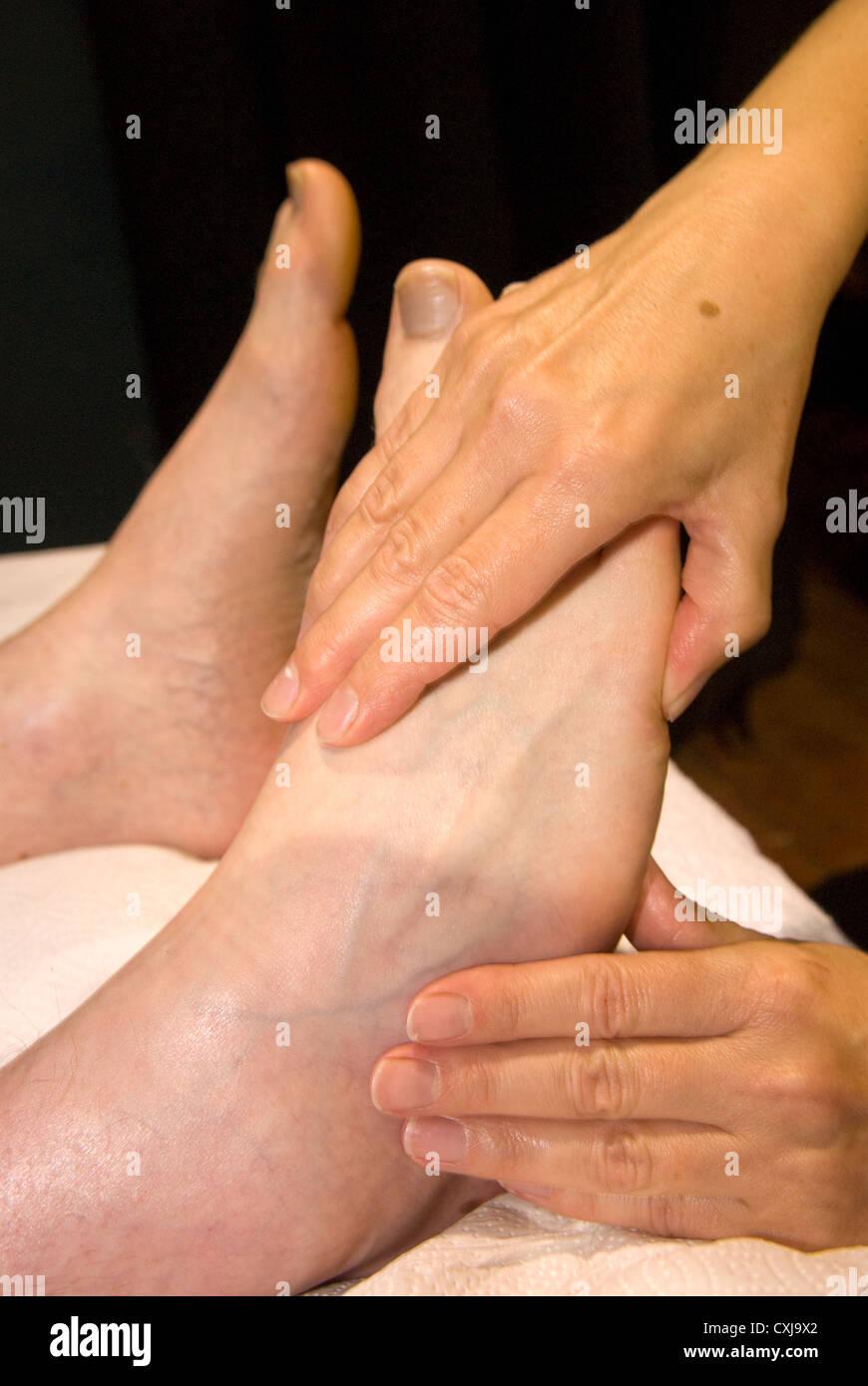Reflexologin am Arbeitsplatz bei einer Veranstaltung von alternativen Therapien, Alton, Hampshire, UK. Stockbild