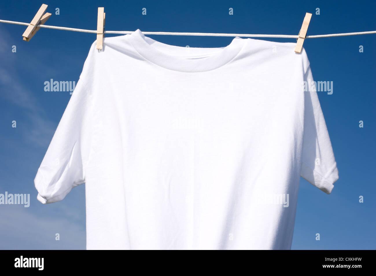 Ein schlichtes weißes T-shirt, eine Wäscheleine hängen, an einem ...
