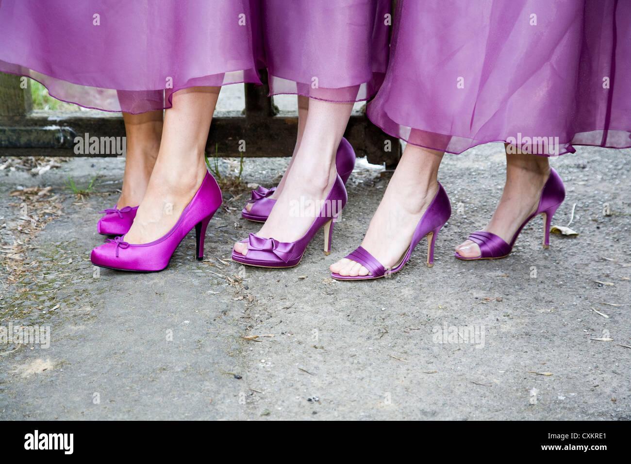 Füße und Knöchel mit lila hochhackige Schuhe zeigen Säume der Kleider Brautjungfer. Stockbild