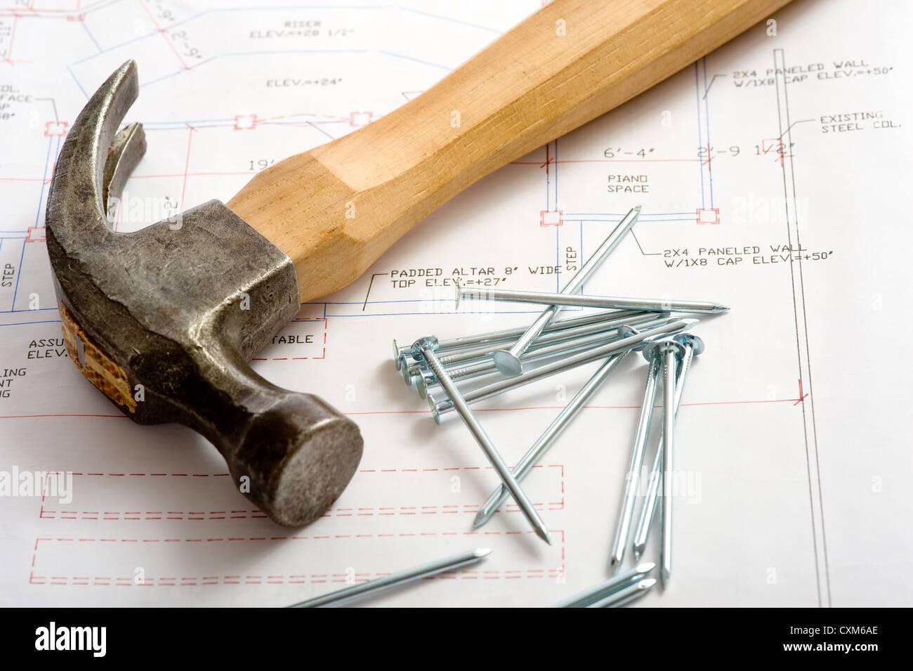 Hammer und Nägel liegen oben auf ein Haus Grundriss oder Blau ...