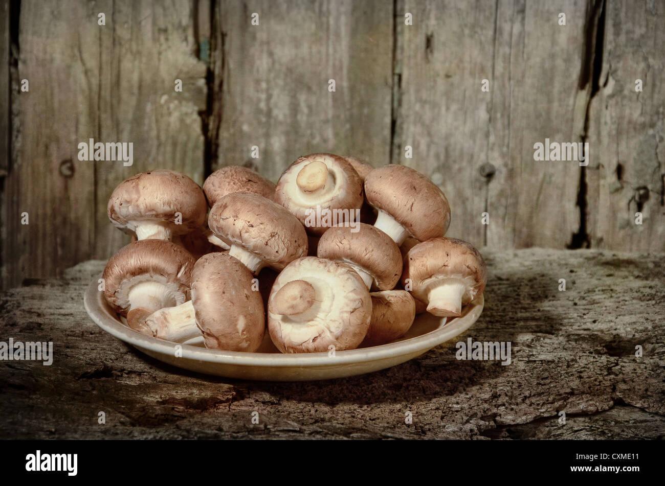 Bio Pilze produzieren braune Champignons roh in einem Teller bereit mit Gabel bereit, alte Tisch gegessen Nahrung Stockbild