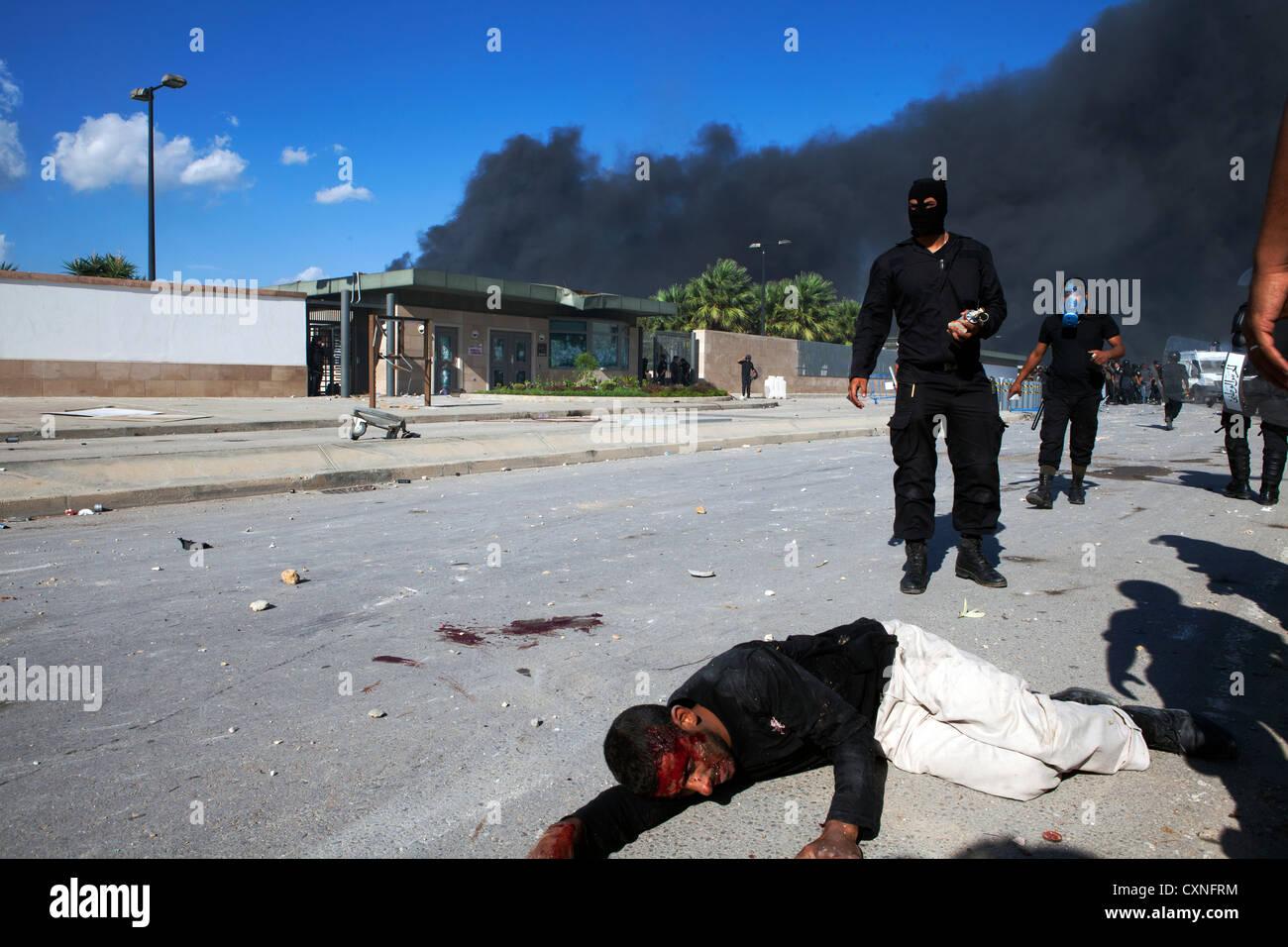 Ein Demonstrant liegt bewusstlos auf dem Boden vor der US-Botschaft in Tunis nach Überfahren einer gepanzerten Stockbild