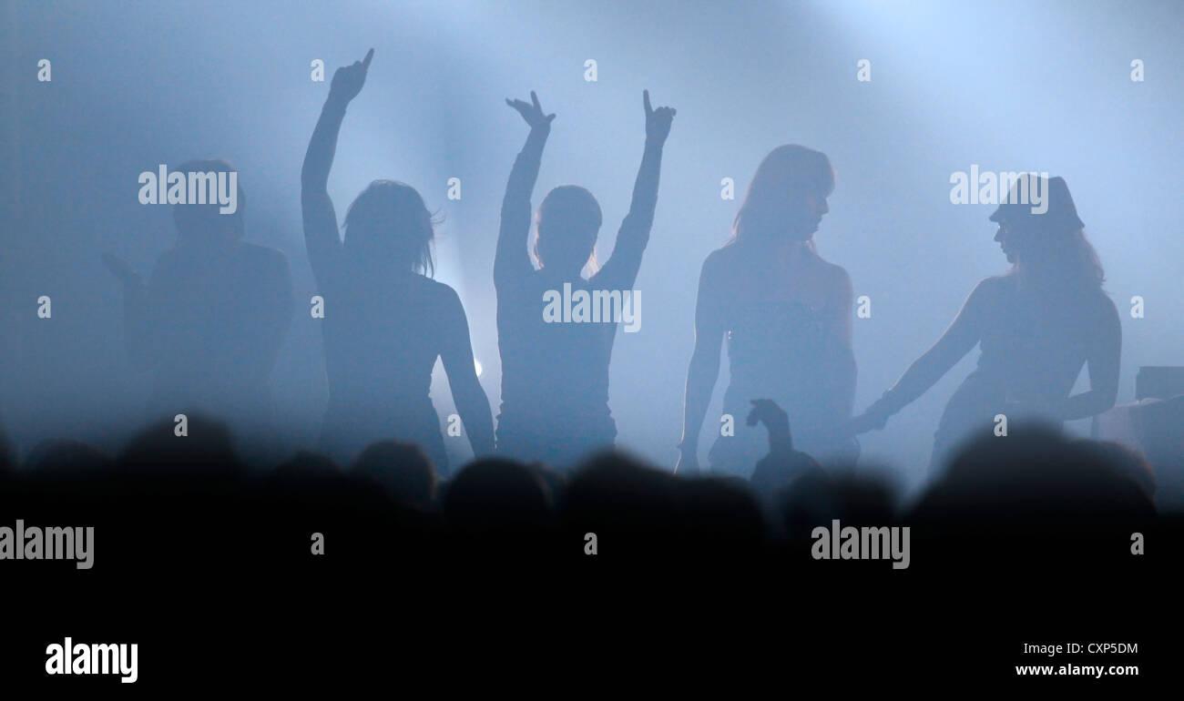 Atmosphäre bei live-Rock-Konzert mit Silhouette weibliche Rocker auf der Bühne mit Arme nach oben in der Stockbild