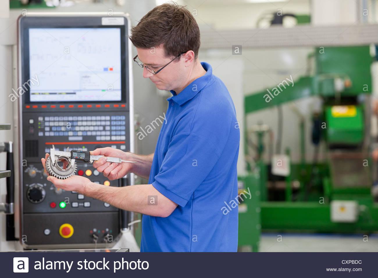 Techniker messen Zahnrad mit Vernier Bremssattel vor Schneidemaschine Drehbank in Hightech-Produktionsanlage Stockfoto