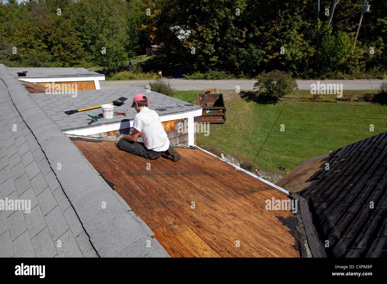 Mann arbeitet auf Hausdach, Reparatur- Stockbild