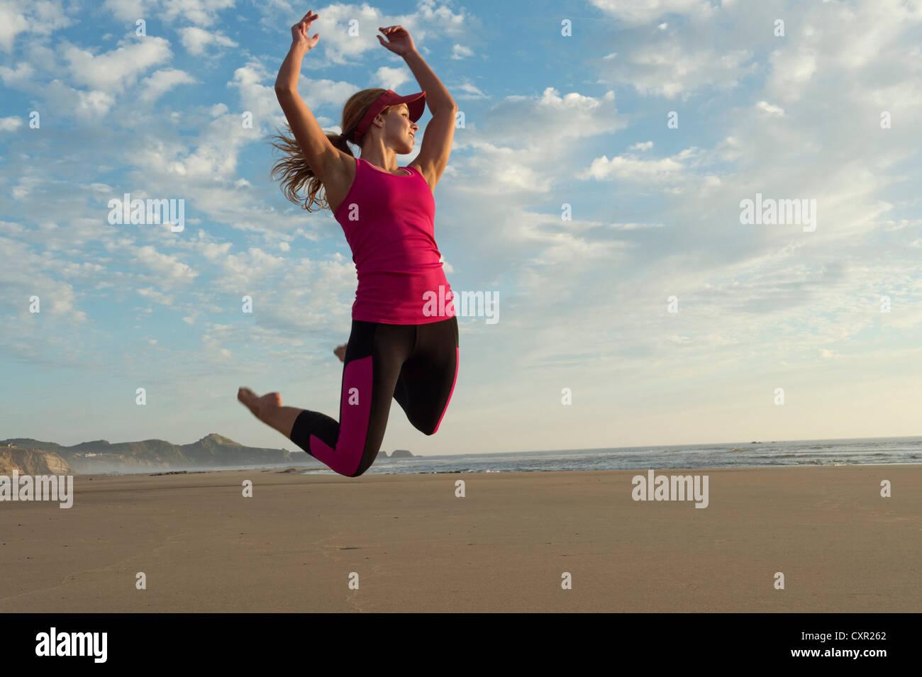 Junge Frau am Strand in die Luft springen Stockbild
