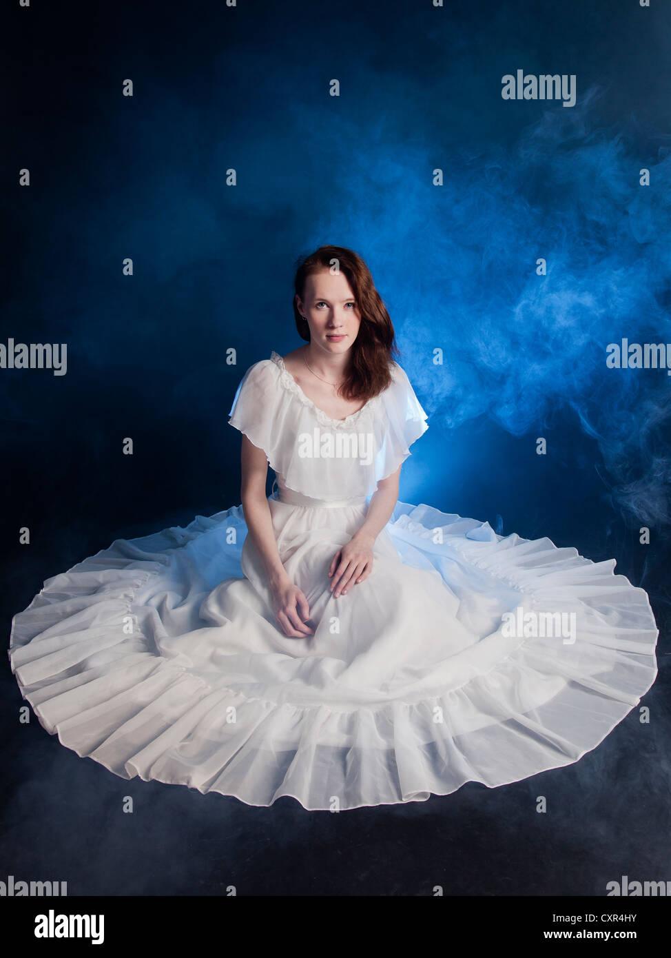 Eine junge Braut Hochzeit Kleid auf Boden blauer Rauch um sie herum ...