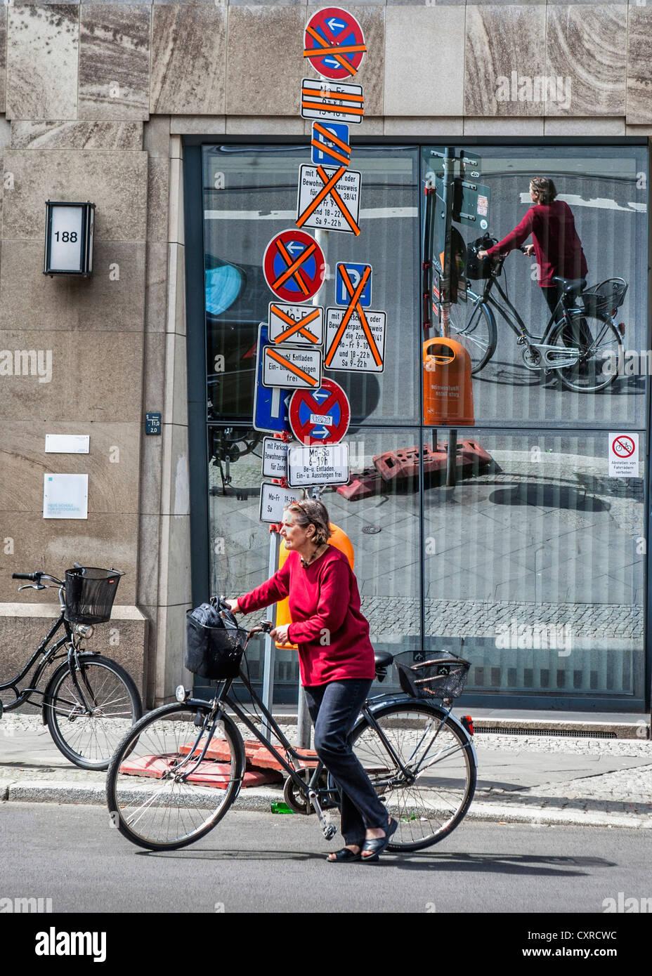 Gemischte Nachrichten von Verkehrszeichen verwechseln Frau Radfahrer in Berlin, Deutschland Stockbild