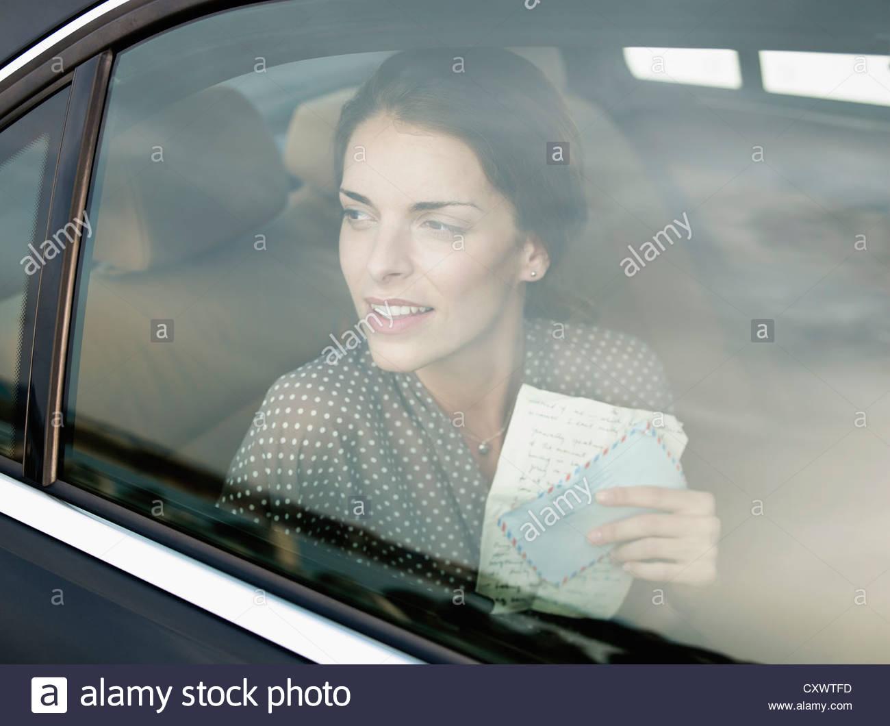 Frau mit Brief im Rücksitz des Autos Stockbild