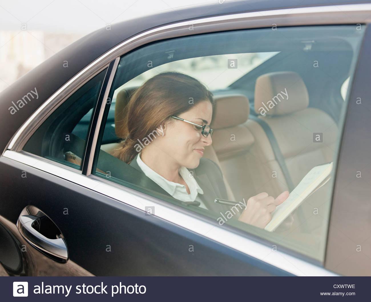 Geschäftsfrau im Rücksitz Auto schreiben Stockbild