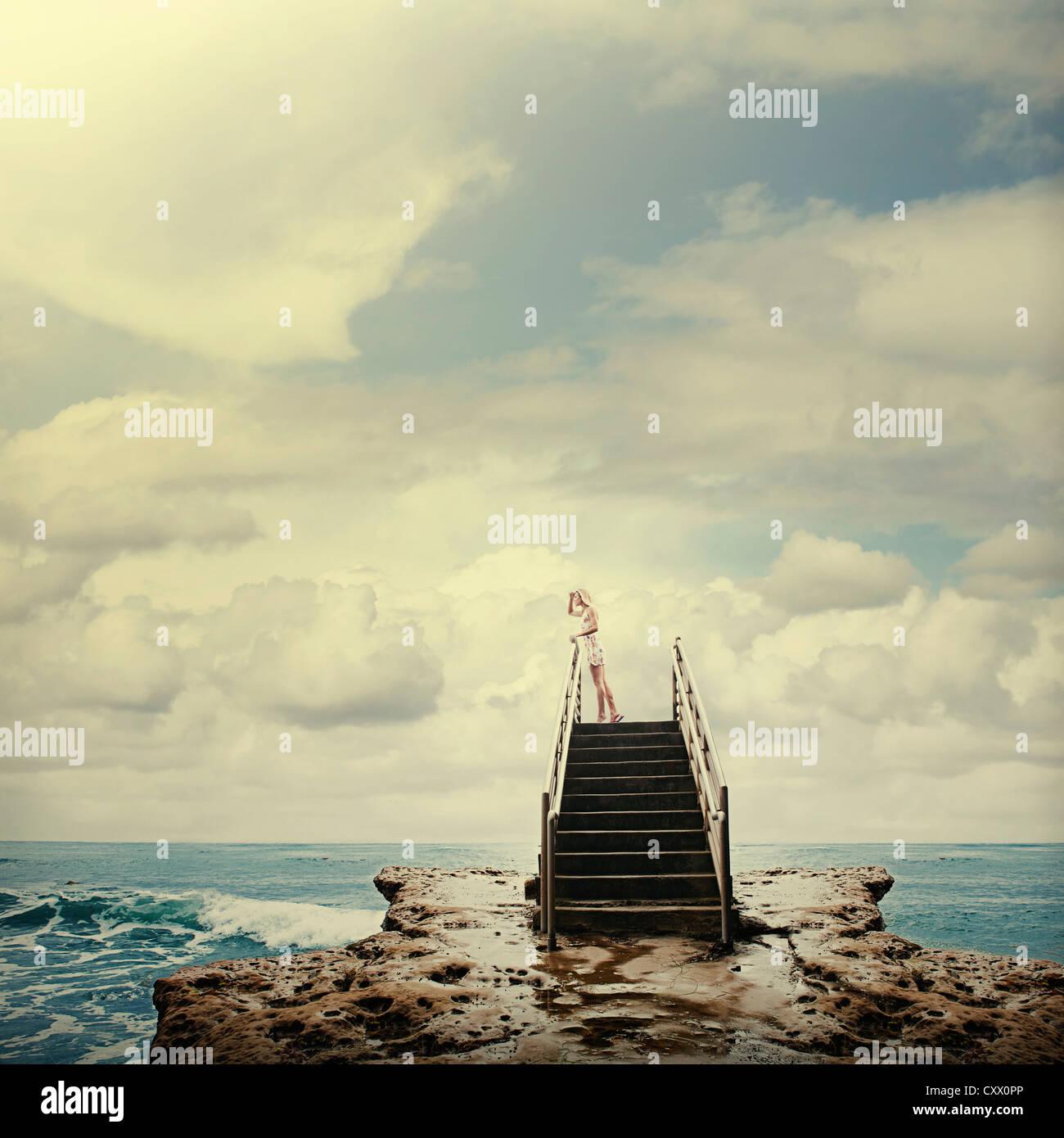 Kaukasische Frau auf der Treppe auf Felsen neben Ozean Stockfoto