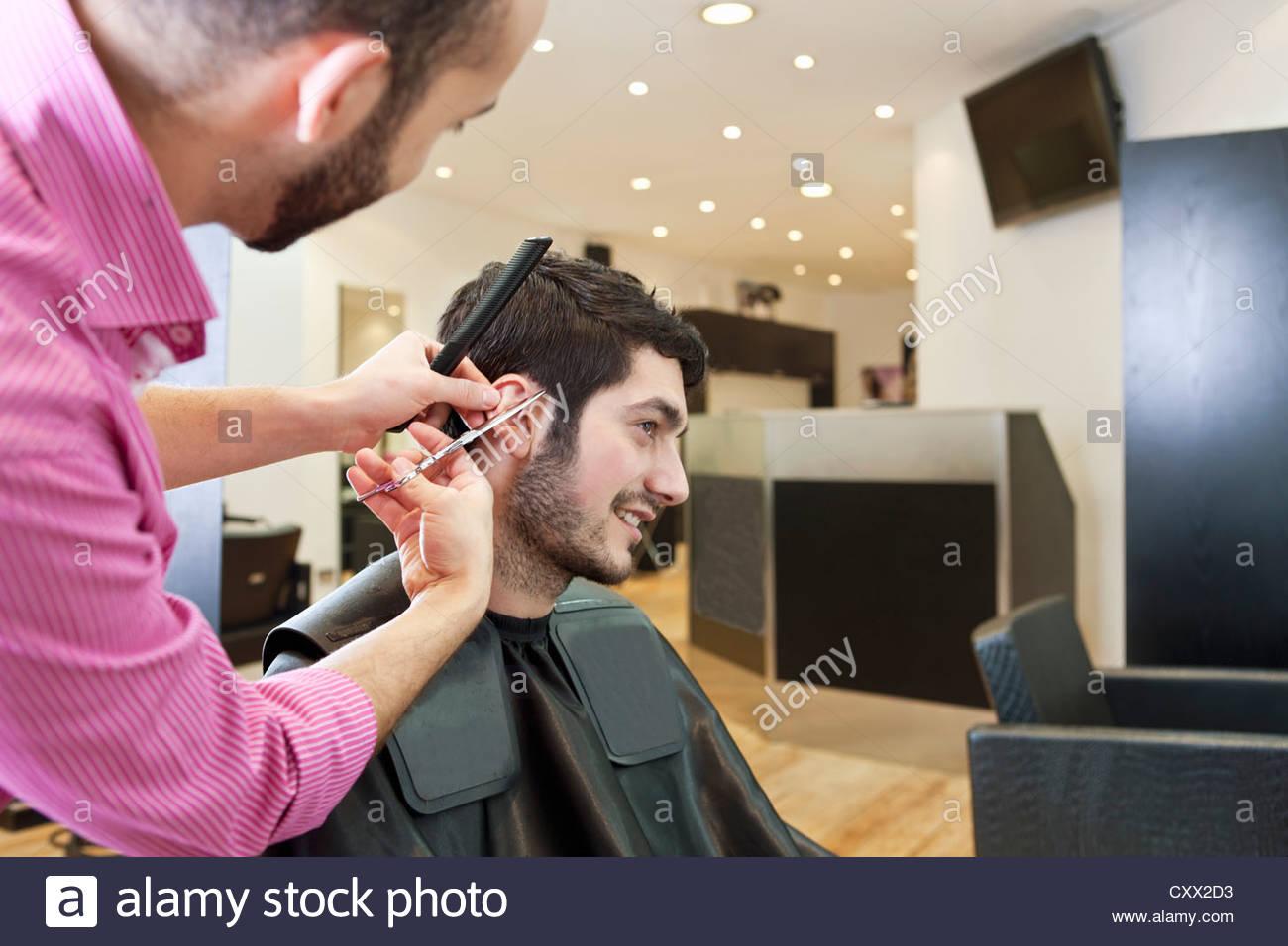Ein männlicher Friseur seine männlichen Klienten Haare mit einer Schere schneiden Stockbild