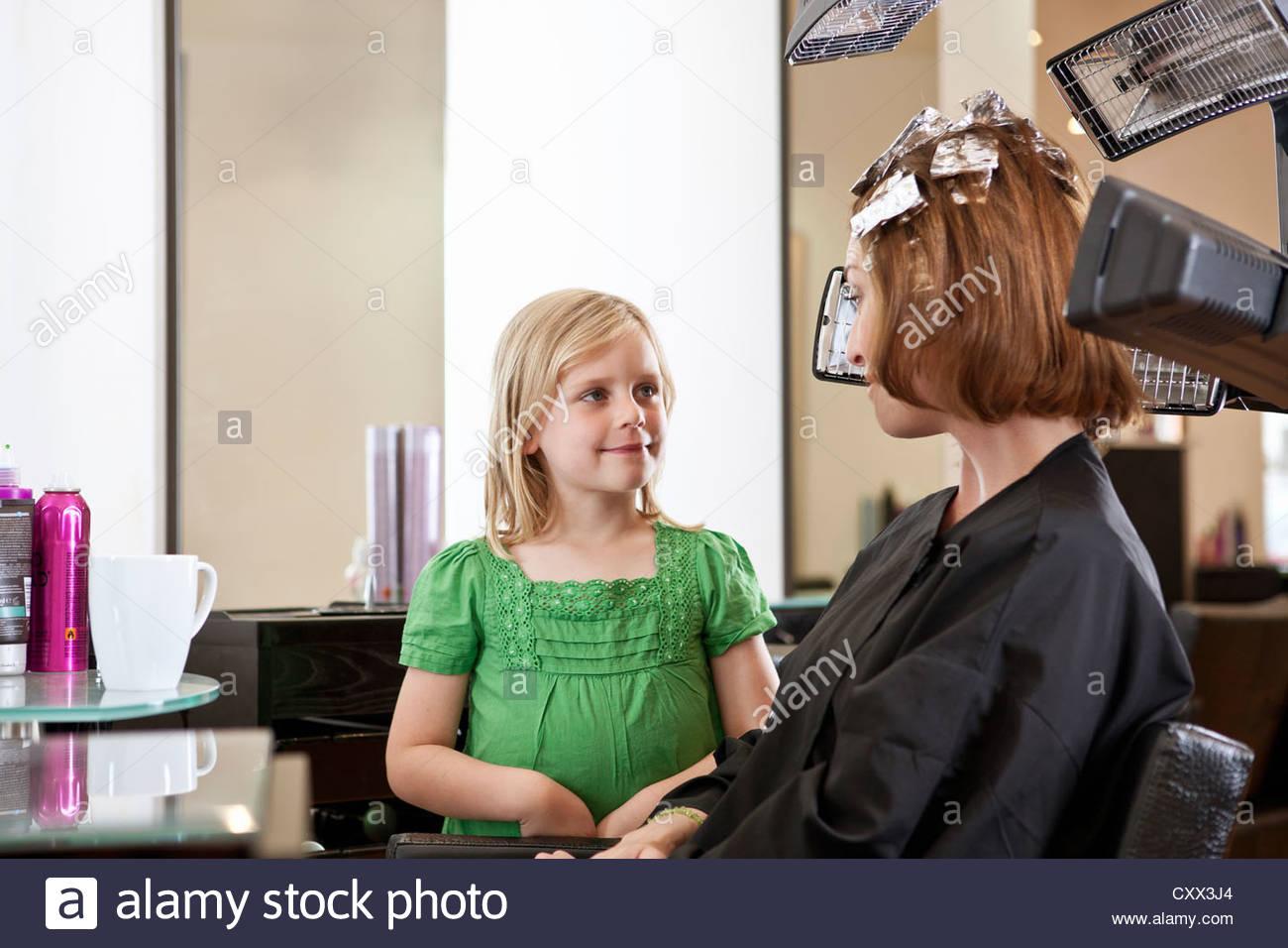 Ein junges Mädchen in einem Friseursalon warten, während ihre Mutter ihr Haar gefärbt hat Stockbild