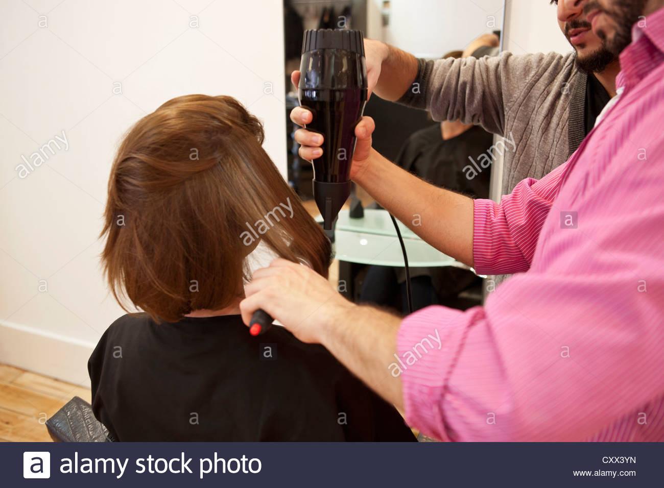 Einen weiblichen Kunden mit Föhnen in einen Friseursalon Stockbild