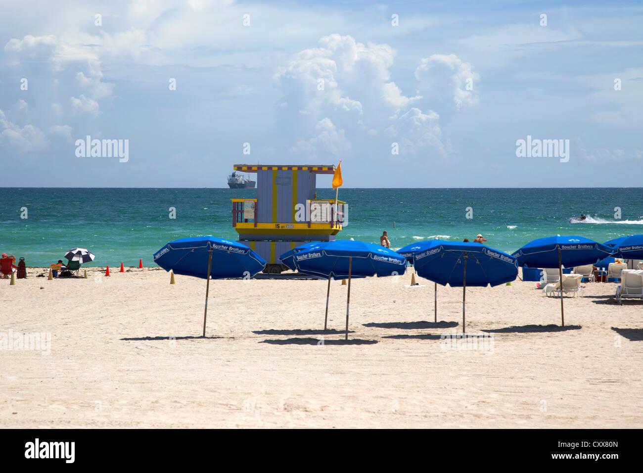 Regenschirme und Sonnenschirme mit Rettungsschwimmer-Turm mit Blick auf Meer Miami south beach Florida usa Stockbild