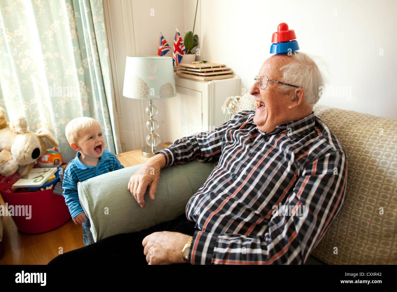 Großvater Spaß mit Enkel zu Hause im Wohnzimmer, da mehr Großeltern zur Betreuung ihrer Enkel, UK Stockbild