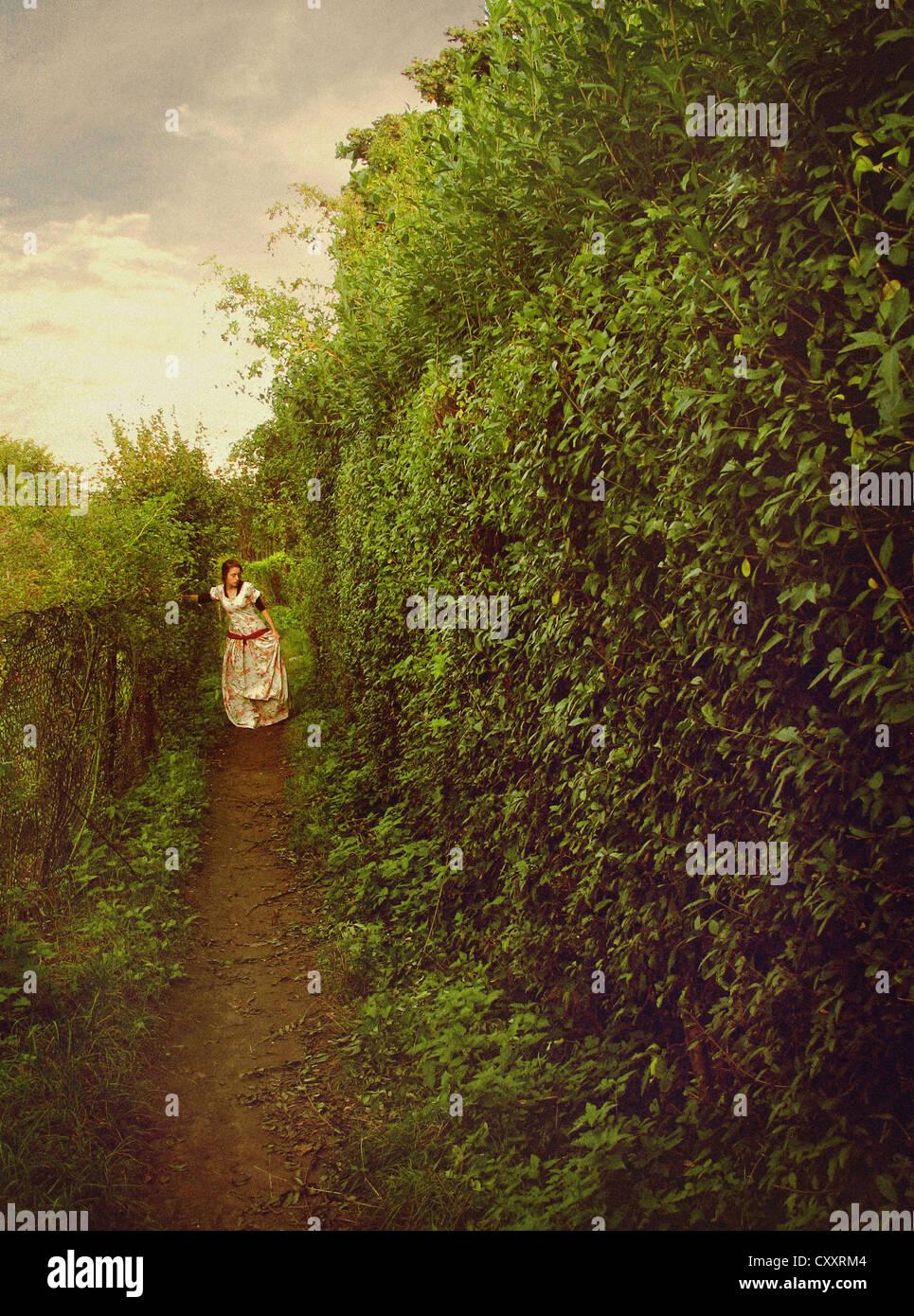Eine Frau in einem weißen Kleid floral, zu Fuß entlang eines Pfades in einem Garten / Labyrinth. Stockfoto